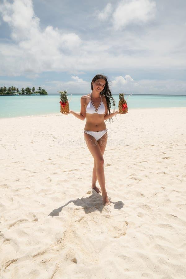 Ein junges Mädchen in einem weißen Badeanzug, der zwei Cocktails Pinots Colada in den Ananas hält stockbild