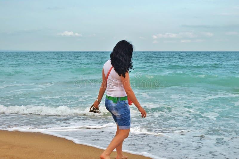 Ein junges Mädchen in einem weißen T-Shirt geht entlang den Sand im Meer Brunette auf dem Ufer des azurblauen Meeres in Bulgarien lizenzfreie stockfotografie