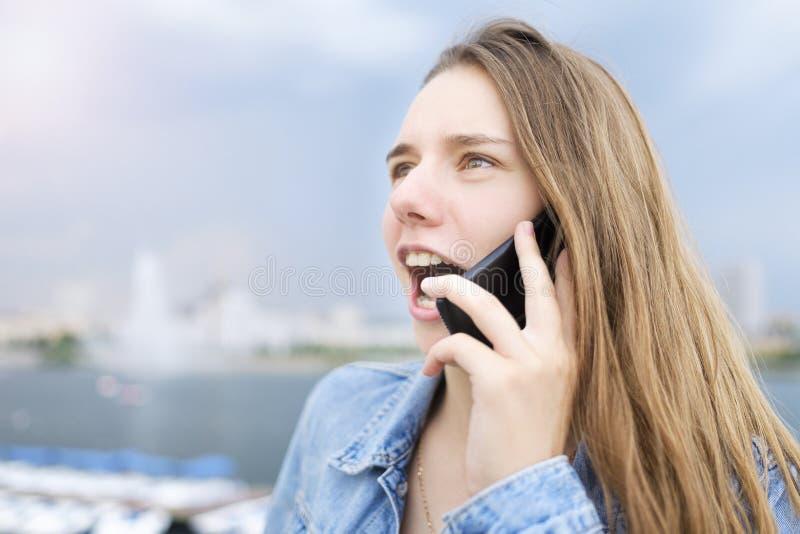 Ein junges Mädchen in einer Denimjacke spricht am Telefon und öffnete ihren Mund in der Überraschung stockbilder