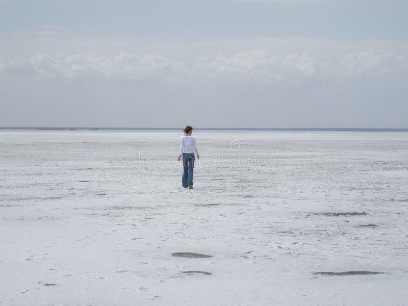Ein junges Mädchen in einer weißen Jacke ist auf einer weißen Wüste Der See wird mit Salz bedeckt lizenzfreie stockfotografie