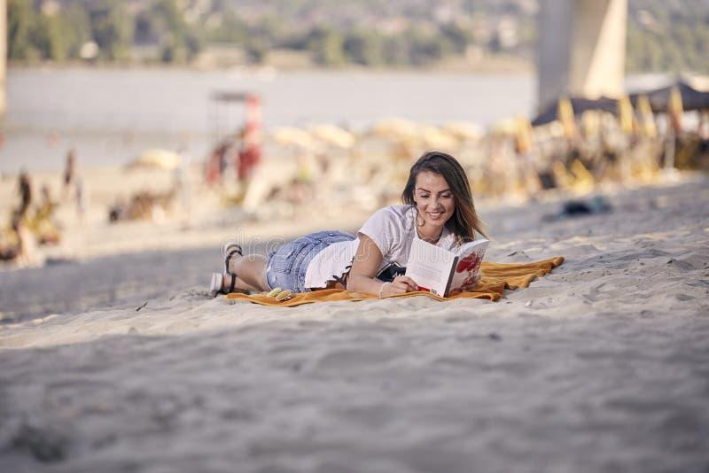 Ein junges Mädchen, entspannende Lesung ein Buch draußen, zufällige Kleidung, stockbild
