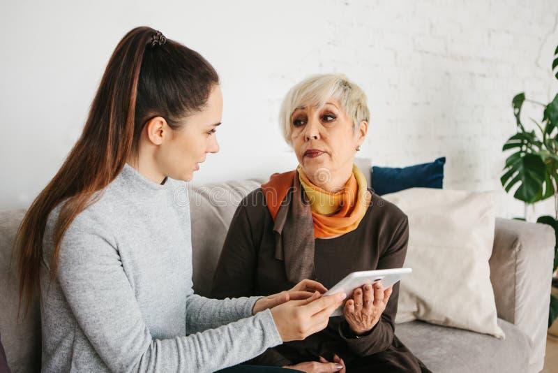 Ein junges Mädchen erklärt einer älteren Frau, wie man eine Tablette benutzt oder zeigt irgendeine Anwendung oder bringt Ihnen be stockbilder