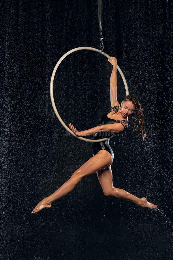 Ein junges Mädchen führt die akrobatischen Elemente im Luftring durch Aqua Studio-Schießenleistungen auf einem schwarzen Hintergr stockbild