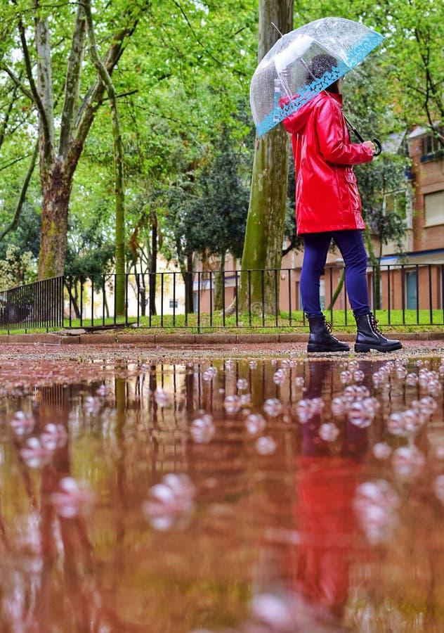 Ein junges Mädchen geht allein an einem regnerischen Tag durch einen Park unter einen Regenschirm stockbild