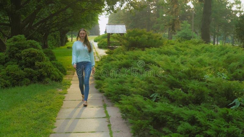 Ein junges Mädchen geht auf die Bahn im Sommerpark lächelnd und freuend stockfotografie