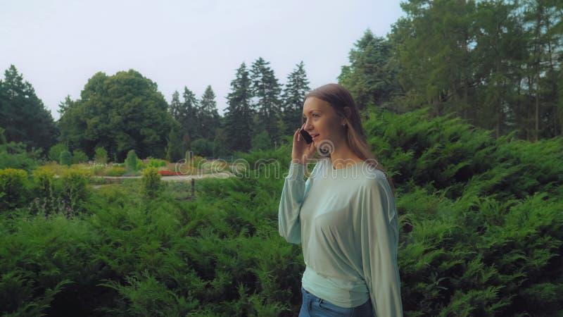 Ein junges Mädchen geht zum Park und zur Unterhaltung am Telefon stockfoto