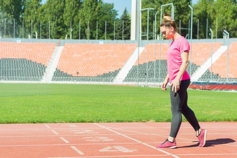 Ein junges Mädchen im Stadion bereitet vor sich zu beginnen lizenzfreie stockfotos