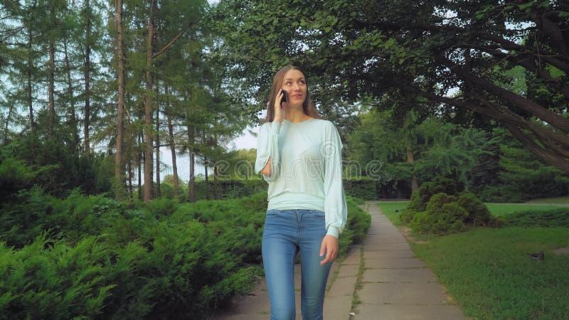 Ein junges Mädchen ist dünner Park und Unterhaltung am Telefon, das Lächeln, überrascht stockbilder
