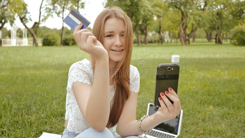 Ein junges Mädchen leistet eine Zahlung in einer on-line-Bank unter Verwendung eines mini magnetischen beweglichen Kartenlesers stockbilder