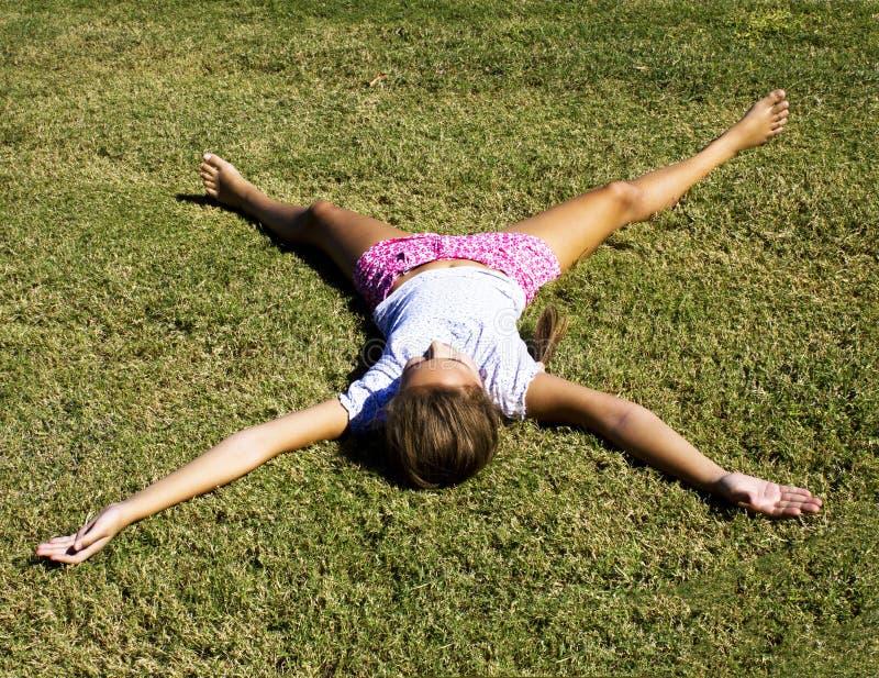 Ein junges Mädchen liegt auf dem gemähten Gras, das ihre Arme und Beine ausdehnt lizenzfreie stockfotos