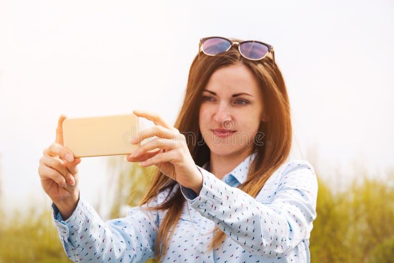 Ein junges Mädchen macht selfie im Park Ein Mädchen macht Fotos von an einem Handy in der Straße lizenzfreies stockfoto