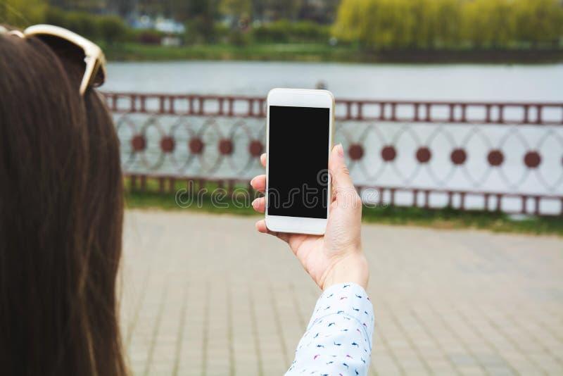 Ein junges Mädchen macht selfie im Park Ein Mädchen macht Fotos von an einem Handy in der Straße stockfotografie