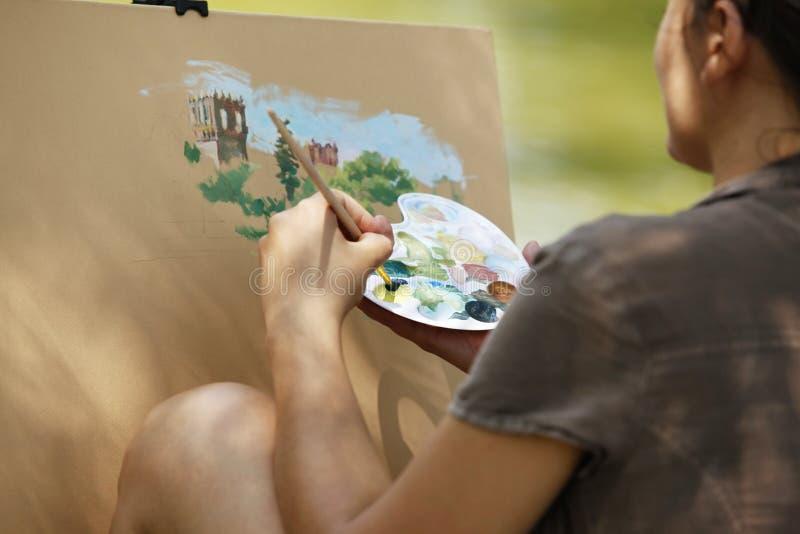 Ein junges Mädchen malt eine Abbildung lizenzfreie stockfotografie