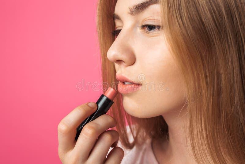 Ein junges Mädchen malt Lippen mit Lippenstift und das Schauen im Spiegel lizenzfreie stockfotografie