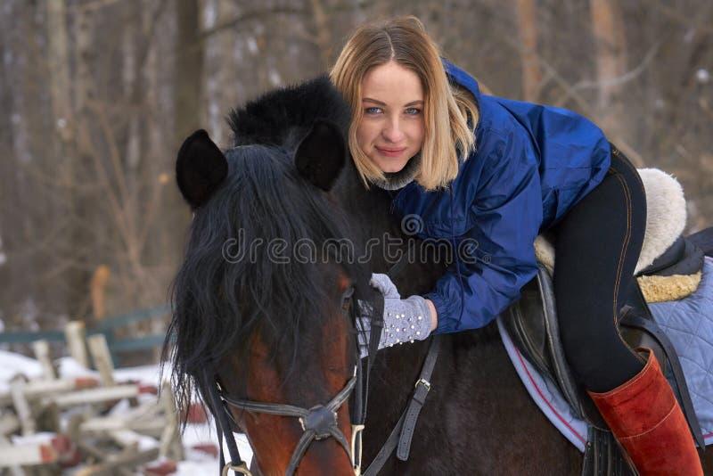Ein junges Mädchen mit dem weißen Haar reitet ein Pferd Das Mädchen umarmt ihr Lieblingspferd Bewölkter Tag des Winters Nahaufnah stockbild