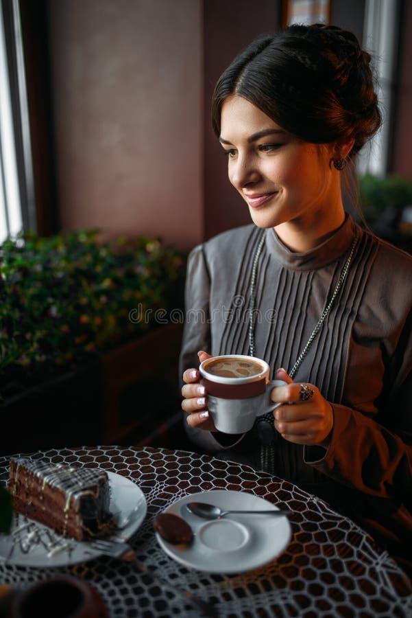Ein junges Mädchen mit einem Tasse Kaffee im Retro- Café lizenzfreie stockfotos