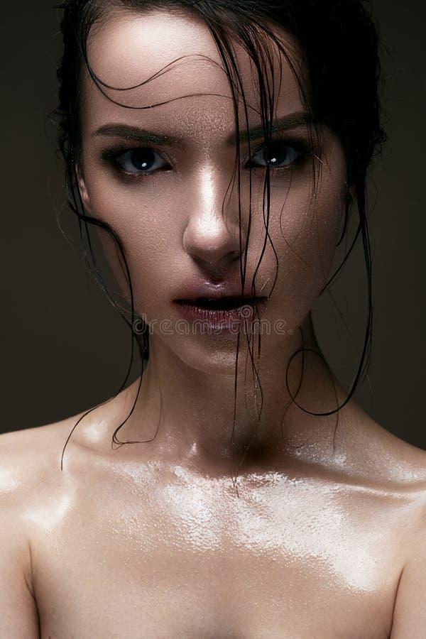 Ein junges Mädchen mit glänzender nasser Haut und dem nassen Haar auf ihrem Gesicht Schönes Modell mit kreativem hellem Make-up S lizenzfreie stockfotos