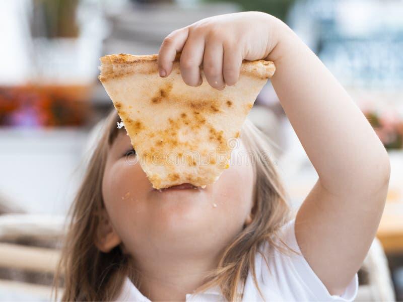 Ein junges Mädchen mit Zöpfen isst ein Stück Pizza horizontal lizenzfreie stockfotos