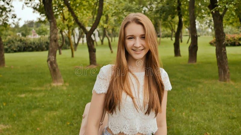 Ein junges Mädchen nimmt an einem Weg im Park teil, betrachtet eine intelligente Uhr auf ihrem Arm und empfängt ein Impulsmaß lizenzfreies stockfoto