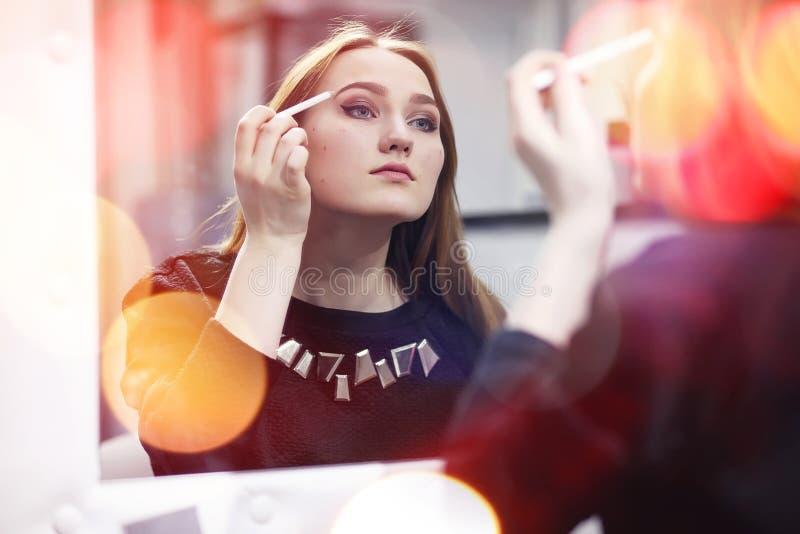 Ein junges Mädchen richtet in einem Schönheitssalon her Das Mädchen in vorderem O lizenzfreies stockbild