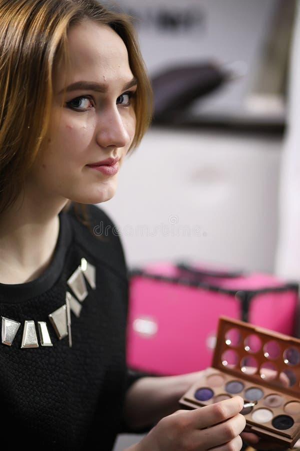 Ein junges Mädchen richtet in einem Schönheitssalon her Das Mädchen in vorderem O lizenzfreie stockfotografie