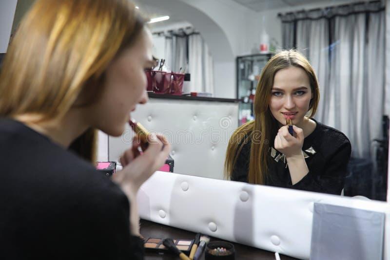 Ein junges Mädchen richtet in einem Schönheitssalon her Das Mädchen in vorderem O stockbild