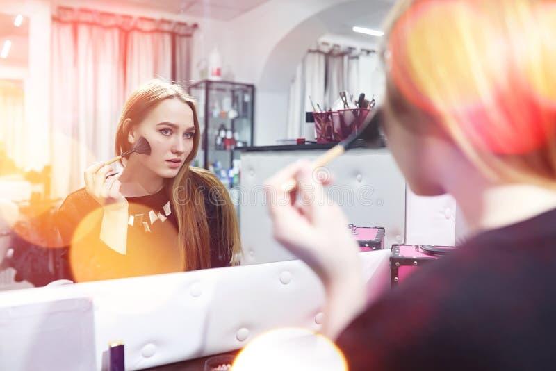 Ein junges Mädchen richtet in einem Schönheitssalon her Das Mädchen in vorderem O stockfotografie