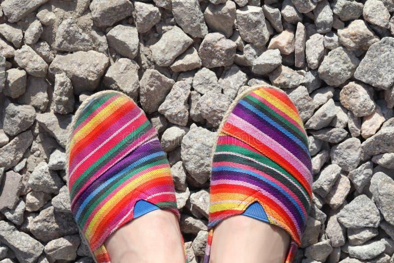 Ein junges Mädchen ` s Füße mit farbigen Schuhen auf Stein lizenzfreie stockfotos
