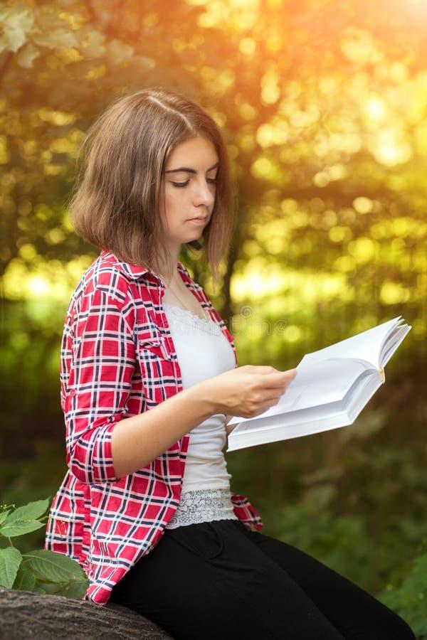 Ein junges Mädchen sitzt draußen auf dem Gras in einem Baum ein Buch, nachdenklichen Blick, ein Sommertag draußen lesend im Park stockfotografie