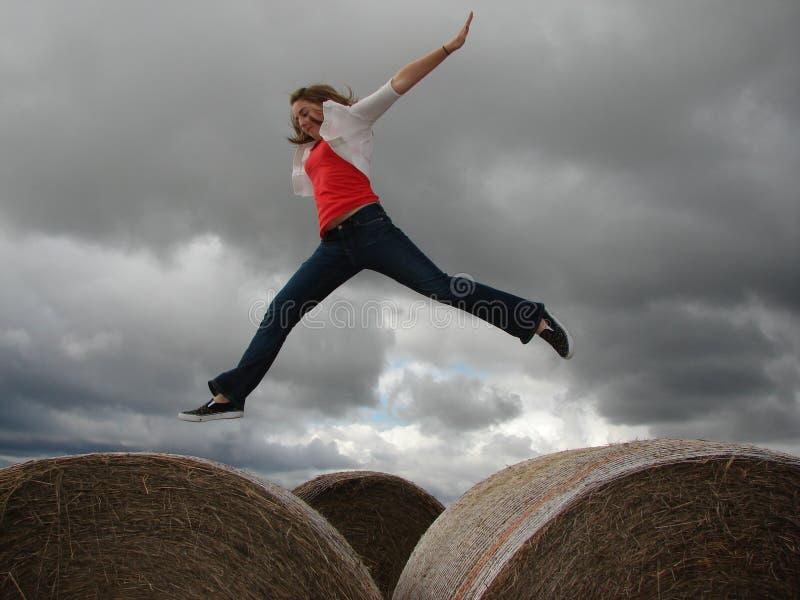 Ein junges Mädchen springt von einem Heuballen zu anderen an einem bewölkten Tag stockfoto