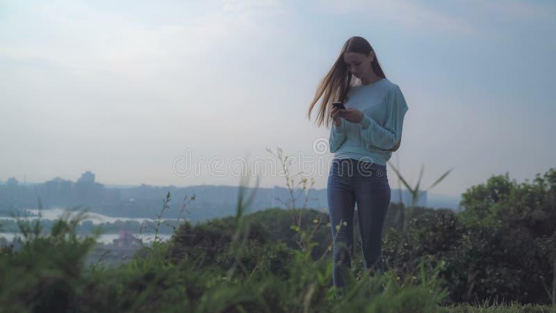 Ein junges Mädchen steht auf einem Hügel und dem Betrachten Ihres Telefons lizenzfreie stockfotos