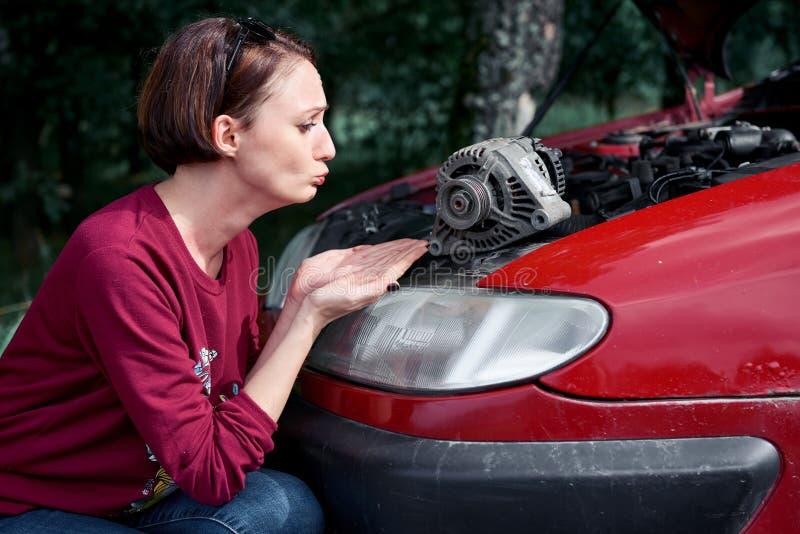 Ein junges Mädchen steht an einem defekten Auto und hält ein schlechtes Ersatzteil, einen elektrischen Generator, versteht nicht, lizenzfreie stockfotos