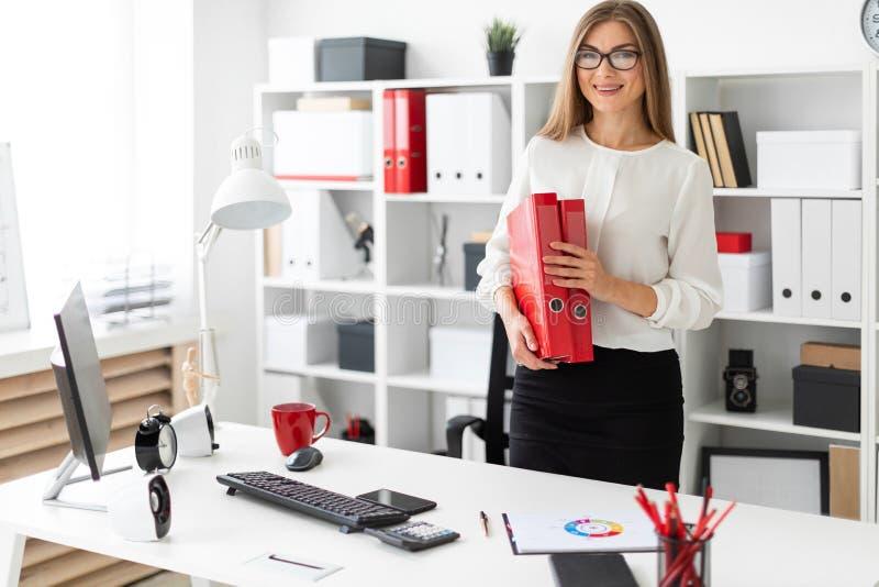 Ein junges Mädchen steht nahe einer Tabelle im Büro und hält einen Ordner mit Dokumenten stockfotos