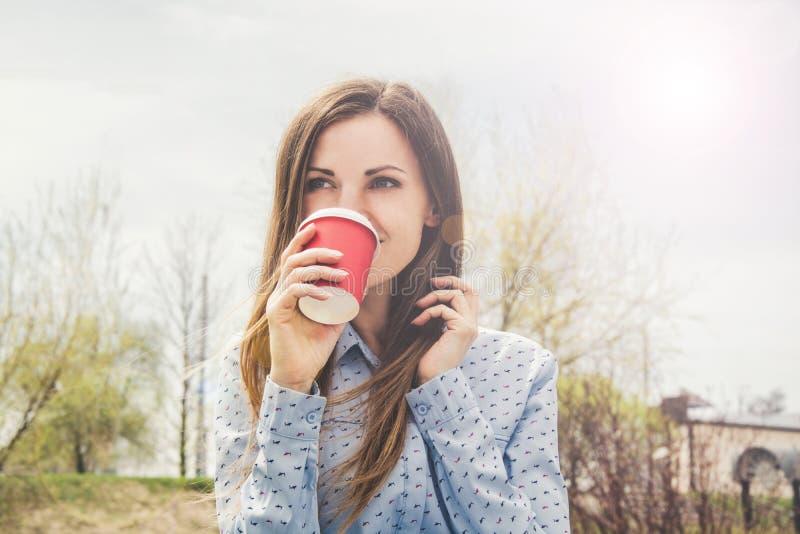 Ein junges Mädchen trinkt Kaffee in der Straße von einer roten Papierschale und vom Lächeln stockfoto