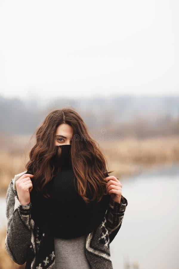 Ein junges Mädchen wirft auf dem Ufer von einem See auf und bedeckt ihr Gesicht mit einem schwarzen Hut stockbilder