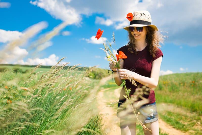 Ein junges M?dchen zupft Blumen einer Mohnblume - sonnigen Tag stockfotos