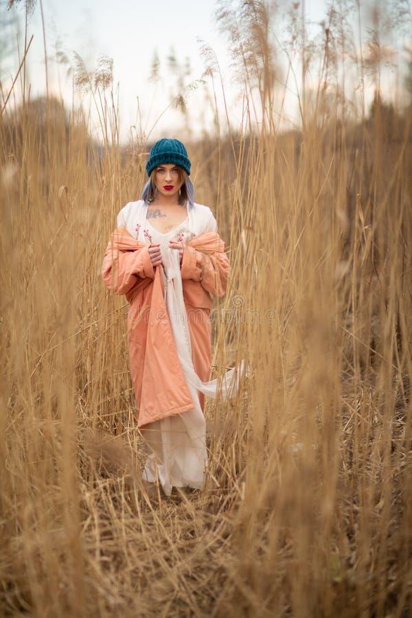 Ein junges M?dchen, das einen Pastellmantel und einen stilvollen Hut tr?gt, wirft auf einem Weizengebiet auf lizenzfreie stockfotografie