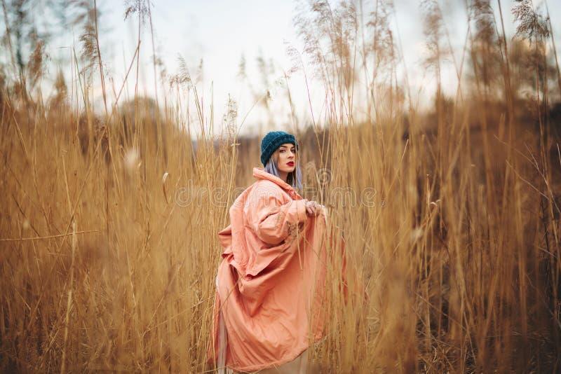 Ein junges M?dchen, das einen Pastellmantel und einen stilvollen Hut tr?gt, wirft auf einem Weizengebiet auf Hinteres viev stockfotos