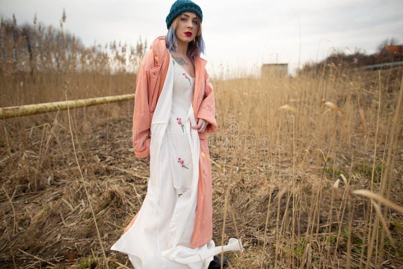 Ein junges M?dchen in einem sch?nen wei?en Kleid und in einem stilvollen Hut wirft auf einem Weizengebiet auf lizenzfreie stockfotografie