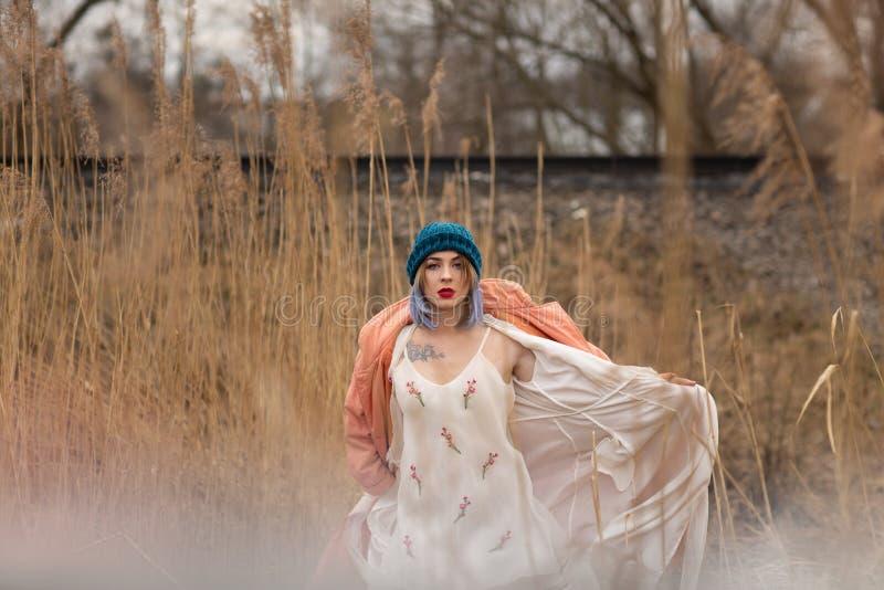 Ein junges M?dchen in einem sch?nen wei?en Kleid und in einem stilvollen Hut wirft auf einem Weizengebiet auf lizenzfreie stockbilder