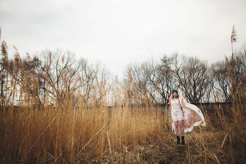 Ein junges M?dchen in einem sch?nen wei?en Kleid und in einem stilvollen Hut wirft auf einem Weizengebiet auf stockbilder
