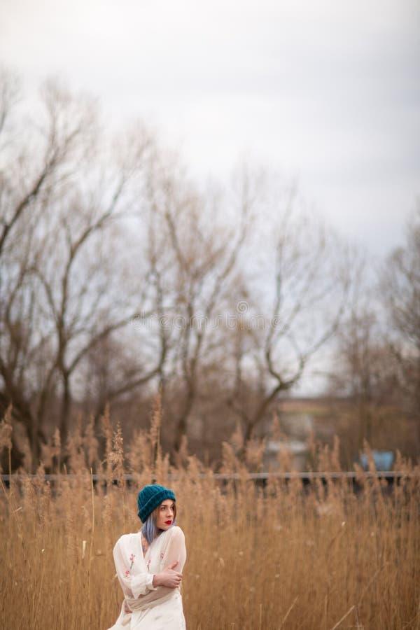 Ein junges M?dchen in einem stilvollen Hut und in einem wei?en Kleid gehend auf einem Weizengebiet lizenzfreie stockfotos