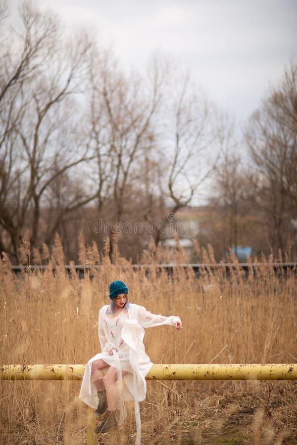 Ein junges M?dchen gekleidet in einem wei?en langen Kleid, sitzend auf einem Rohr, nahe einem Weizenfeld lizenzfreie stockfotos