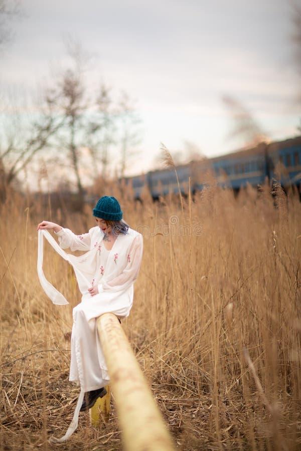 Ein junges M?dchen gekleidet in einem wei?en langen Kleid, sitzend auf einem Rohr, nahe einem Weizenfeld Hinter ihr ist ein Zug lizenzfreies stockbild