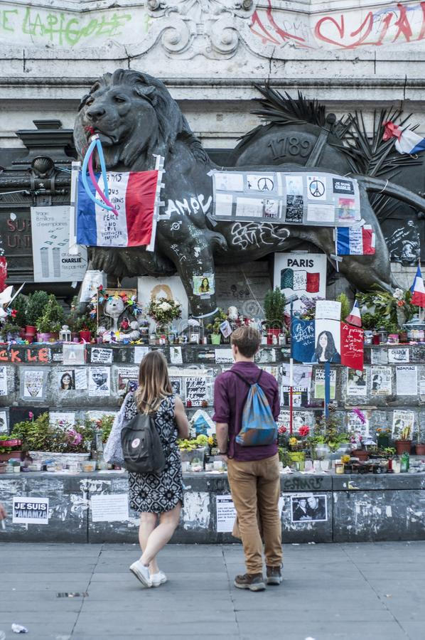 Ein junges Paar betrachtet die Ehrerbietungen, die beim Place de la Republique gelassen werden stockfotografie