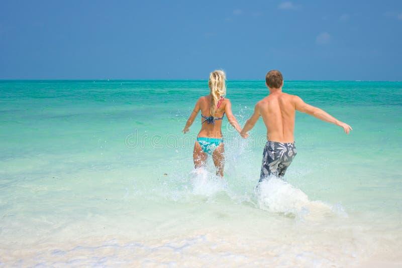 Ein junges Paar, das durch die Wellen geht stockfotografie