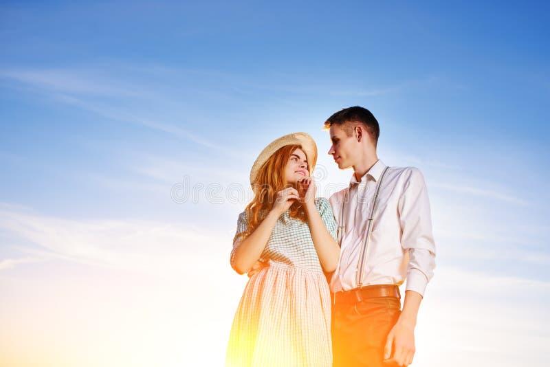 Ein junges Paar, das gegen einen Hintergrund des blauen Himmels steht stockfoto