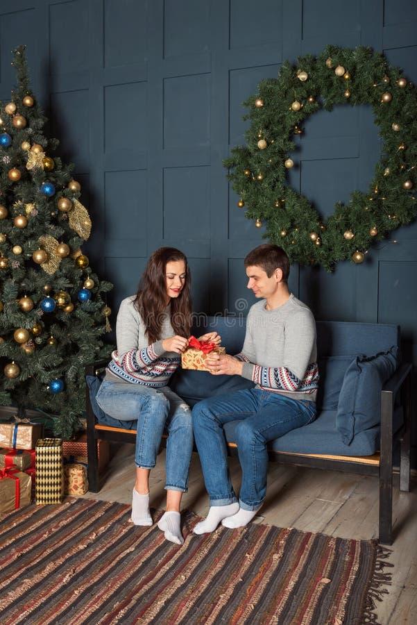 Ein junges Paar in den identischen Strickjacken sitzen auf dem Sofa nahe dem Weihnachtsbaum und betrachten eine Geschenkbox stockbild