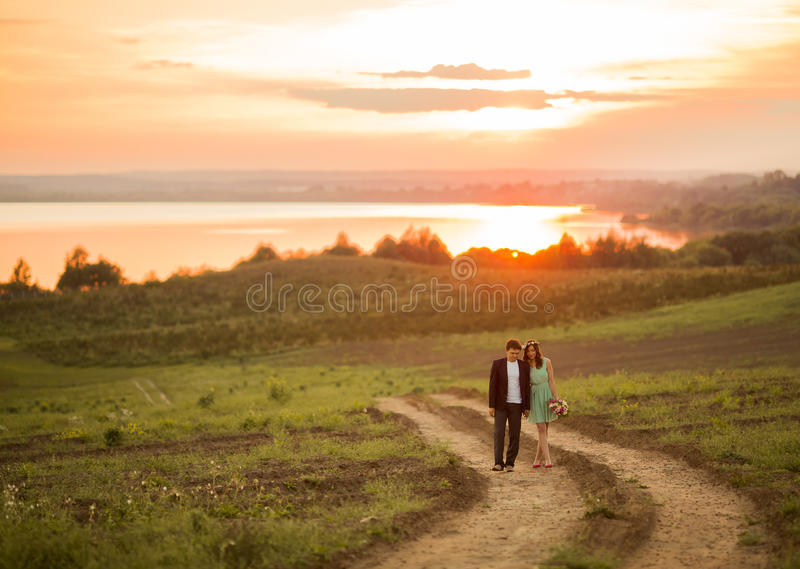 Ein junges Paar in der Liebe im Freien bei dem Sonnenuntergang stockbild