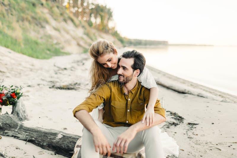 Ein junges Paar hat Spaß und umarmt auf dem Strand Schönes Mädchen umfassen ihren Freund von der Rückseite Wedding Weg A stockbilder